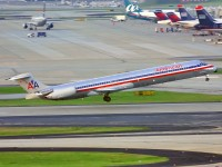 With US Airways tails in the distance, this American Airlines MD-82 departs from Atlanta.  Photo:  Mark Plumley - OPShots.net  //